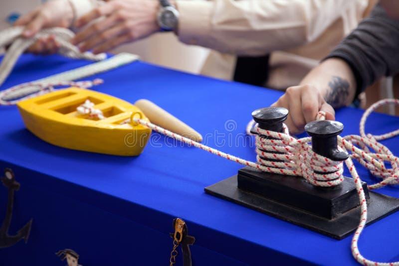 Ungar som lär att förtöja på leksakskeppmodell på seglingskolan royaltyfria bilder
