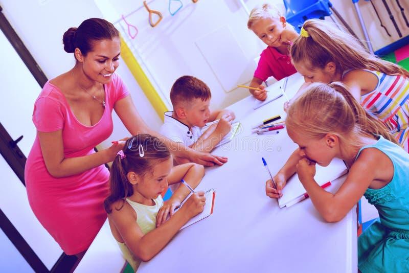 Ungar som lär att skriva på kurs i grundskolagrupp royaltyfria bilder