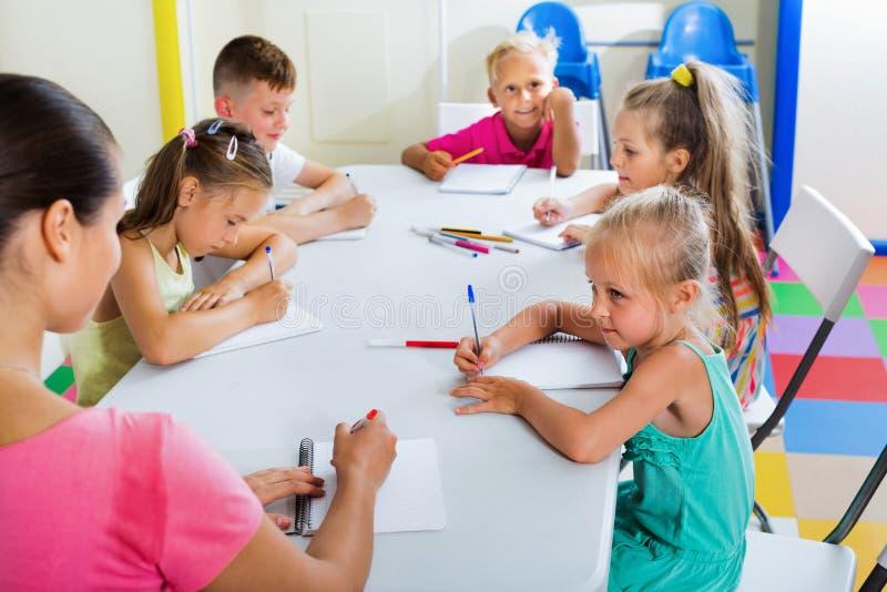 Ungar som lär att skriva på kurs i grundskolagrupp arkivfoto