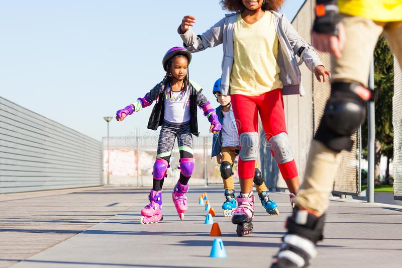 Ungar som lär till slalom, åker skridskor med inline skridskor royaltyfria bilder