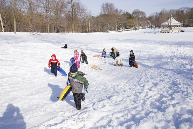 Ungar som leker i snow arkivfoton