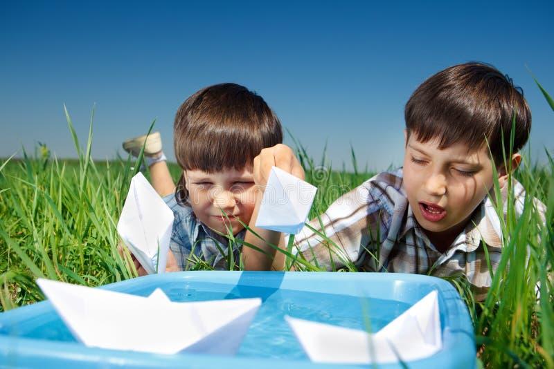 Ungar som leker med pappers- fartyg arkivfoton