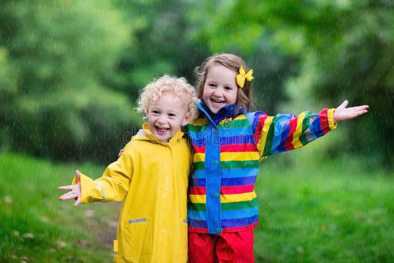 ungar som leker regn royaltyfria foton