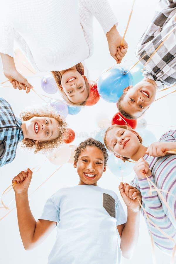 Ungar som ler och rymmer ballonger arkivbilder