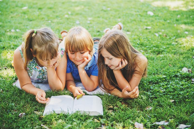 Ungar som ligger på grönt gräs och läs- berättelse, bokar royaltyfria foton