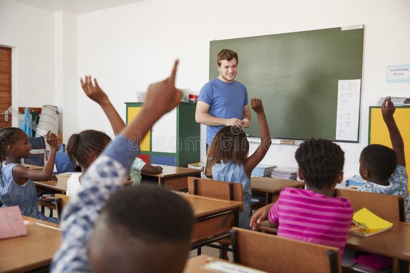 Ungar som lyfter händer till läraren i en grundskolagrupp royaltyfria foton
