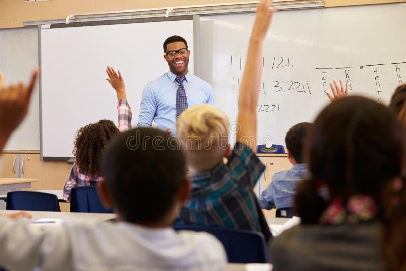 Ungar som lyfter händer till svaret i en grundskolagrupp royaltyfri fotografi