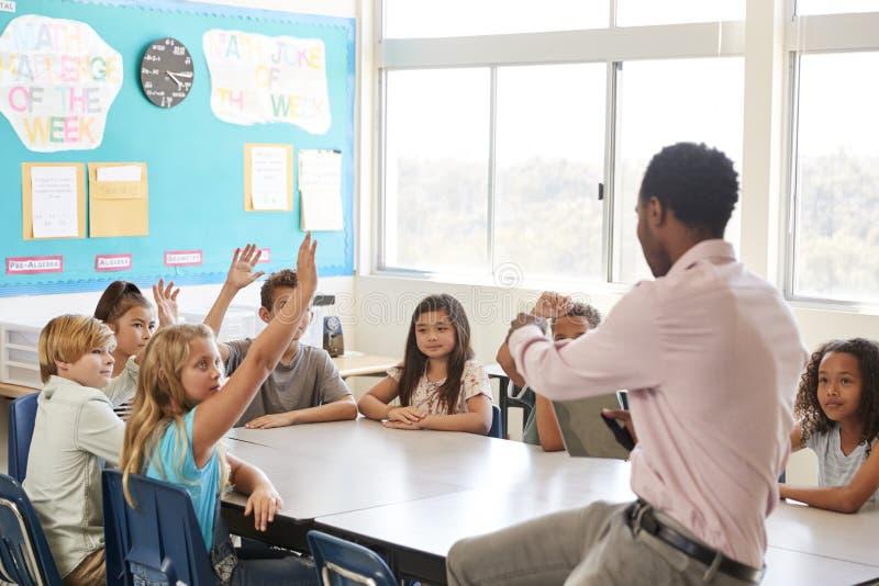 Ungar som lyfter händer till svaret i en grundskolakurs royaltyfria foton
