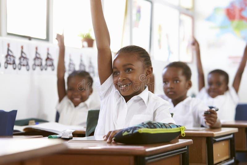Ungar som lyfter händer under en kurs på en grundskola royaltyfri fotografi