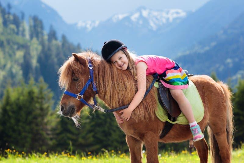 Ungar som rider ponnyn Barn på häst i fjällängberg royaltyfri fotografi
