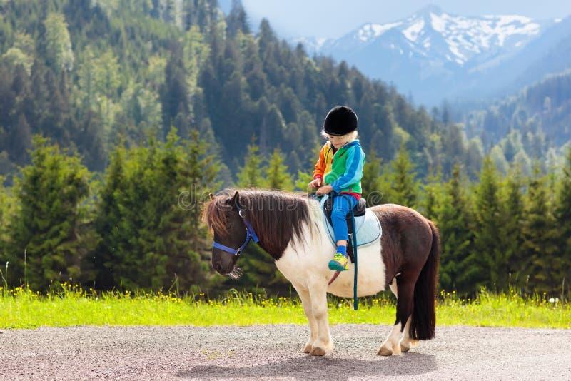 Ungar som rider ponnyn Barn på häst i fjällängberg royaltyfria bilder