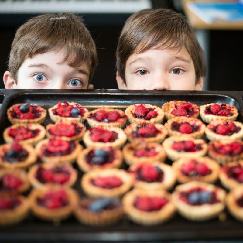 Ungar som ser förberedelsen av muffin arkivbilder