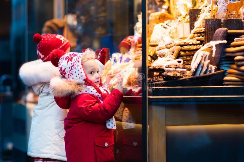 Ungar som ser godisen och bakelse på jul, marknadsför royaltyfri bild