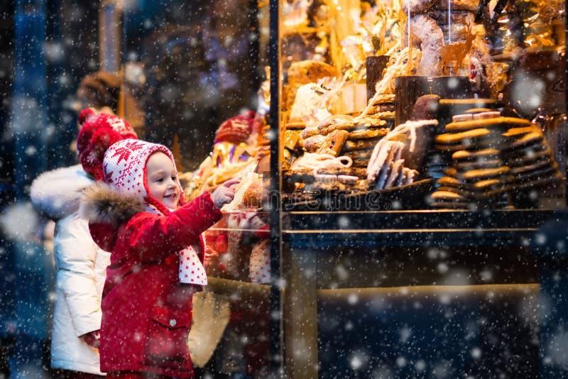 Ungar som ser godisen och bakelse på jul, marknadsför arkivfoto