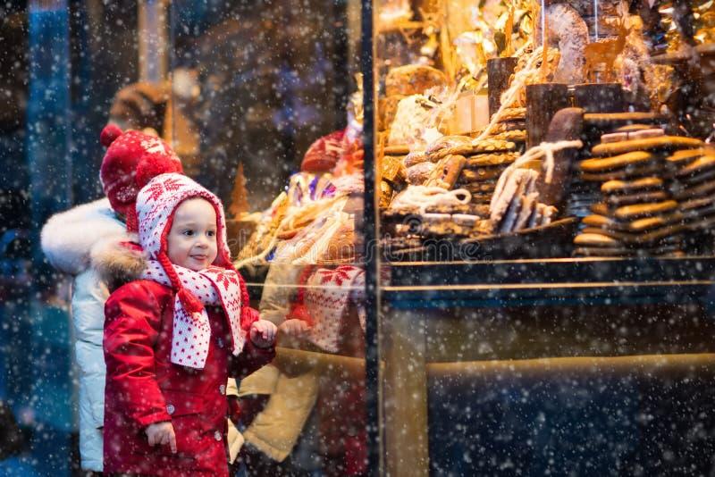 Ungar som ser godisen och bakelse på jul, marknadsför arkivbilder