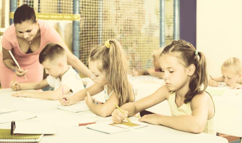 Ungar som sitter, och lyssnande lärare i grundskola royaltyfria foton