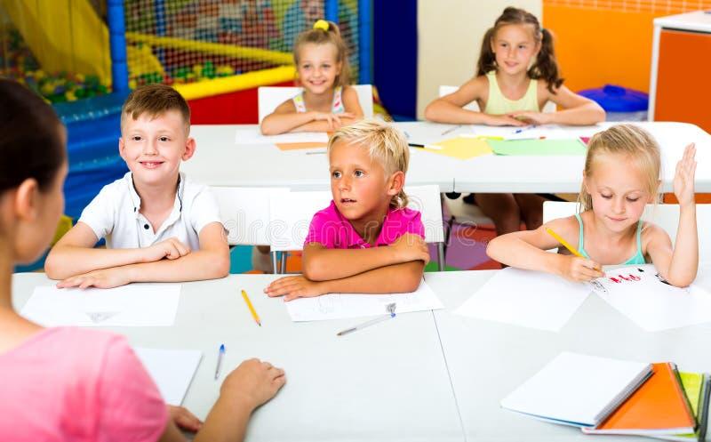 Ungar som sitter, och lyssnande lärare i grundskola royaltyfri bild