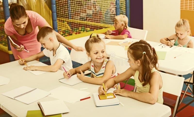 Ungar som sitter, och lyssnande lärare i grundskola arkivbild