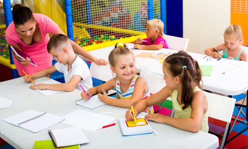 Ungar som sitter, och lyssnande lärare i grundskola royaltyfri foto