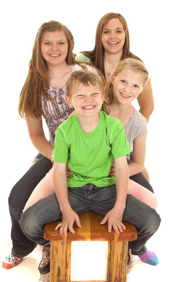 Ungar som sitter på att le för bänk fotografering för bildbyråer