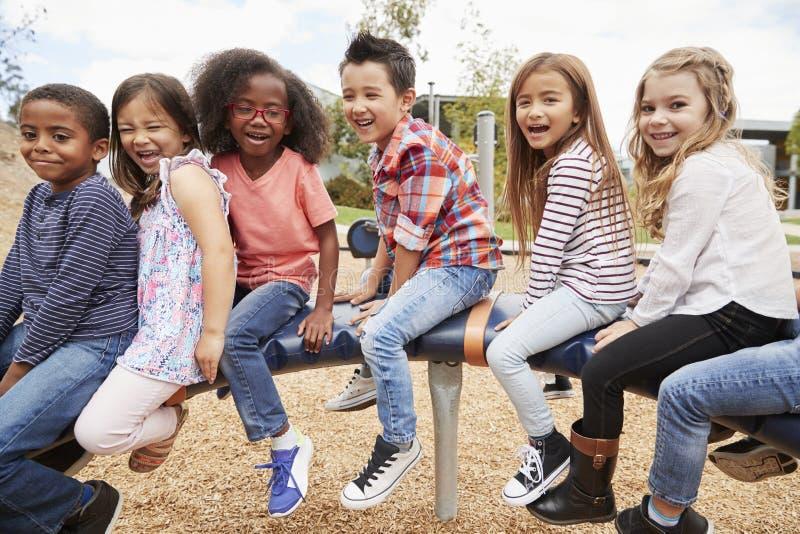Ungar som sitter på en karusell i deras schoolyard, sidosikt arkivbilder