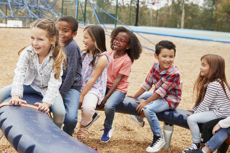 Ungar som sitter på en snurrkarusell i deras schoolyard royaltyfri foto