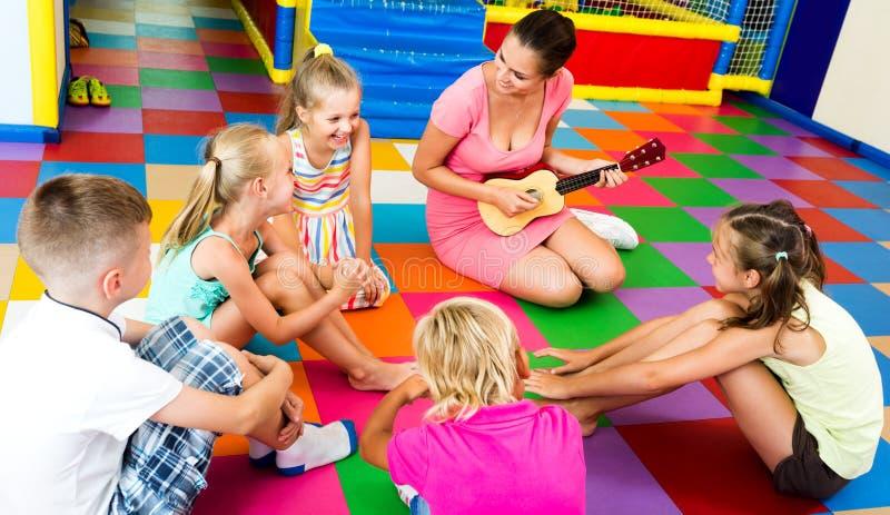 Ungar som sitter runt om lärare med den lilla gitarren royaltyfri foto