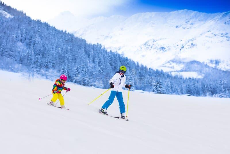 Ungar som skidar i bergen arkivfoton