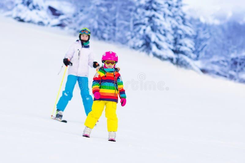 Ungar som skidar i bergen arkivbilder