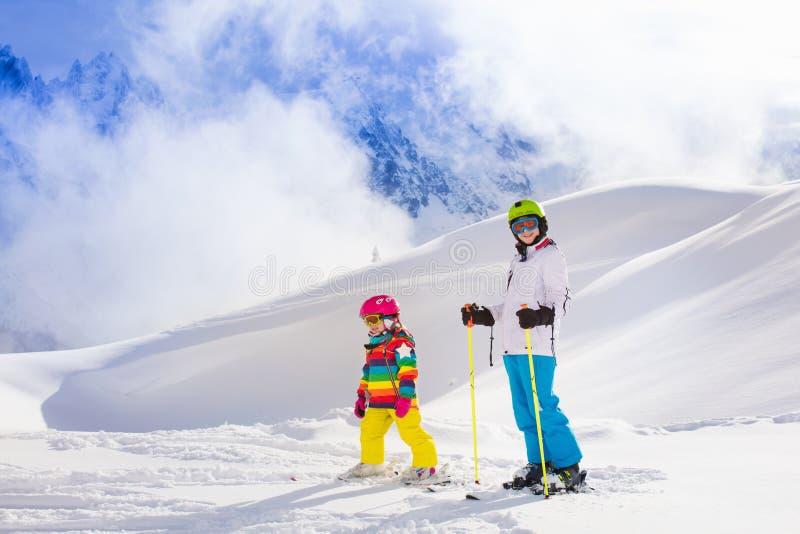 Ungar som skidar i bergen fotografering för bildbyråer
