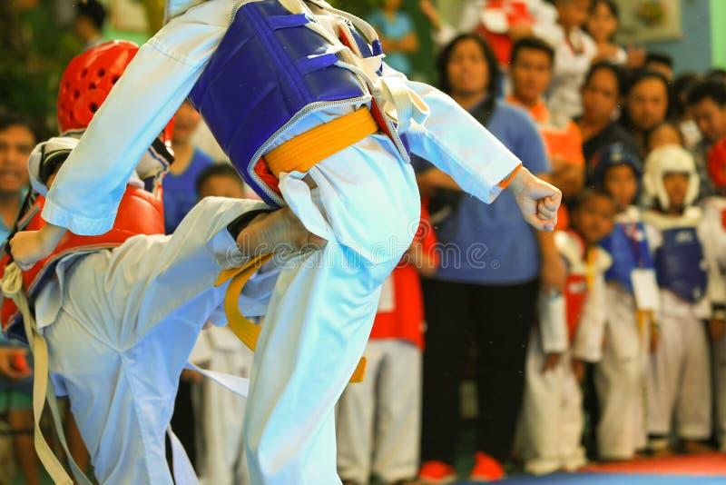 Ungar som slåss på etapp under den Taekwondo striden royaltyfri foto
