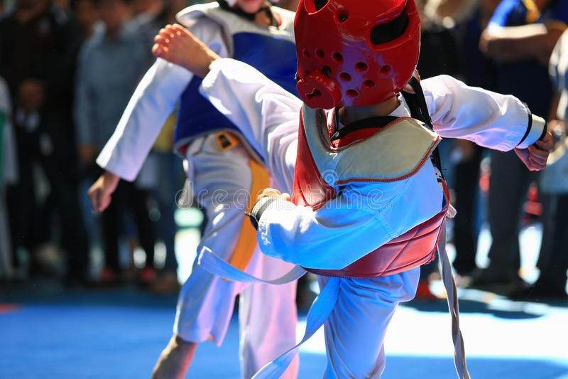 Ungar som slåss på etapp under den Taekwondo striden arkivfoto