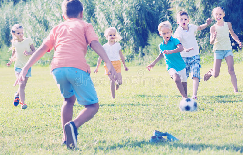 Ungar som sparkar fotboll parkerar in arkivbild