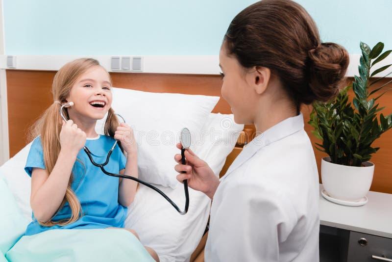 Ungar som spelar doktorn och patienten med stetoskopet i sjukhus arkivbild
