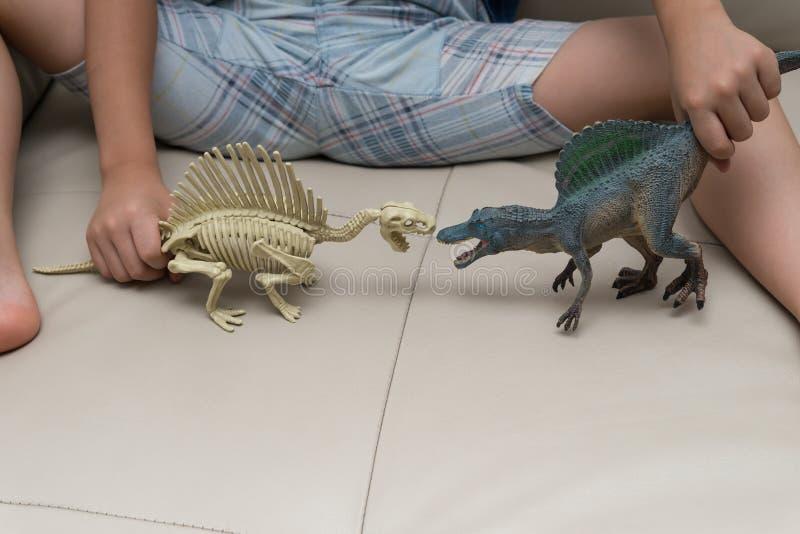 Ungar som spelar en Spinosaurus leksak och ett Spinosaurus skelett royaltyfri bild