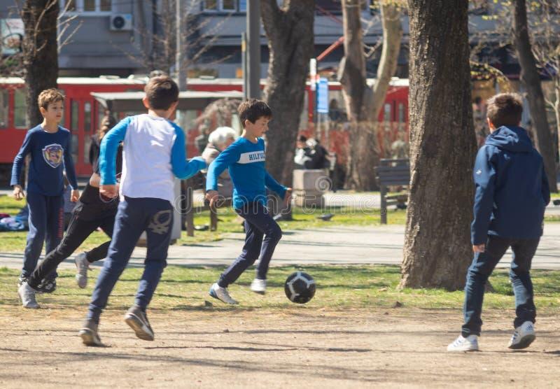 Ungar som spelar fotboll i, parkerar på en solig dag royaltyfria foton