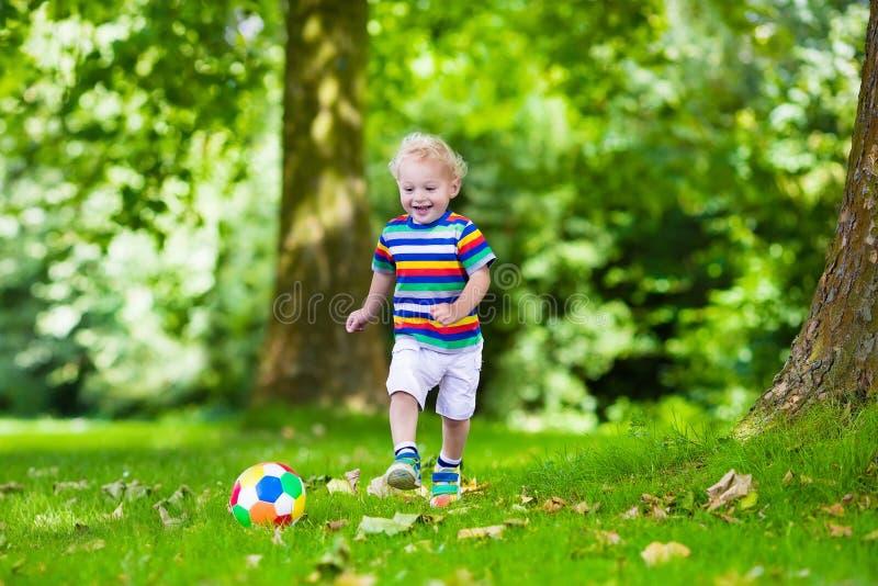 Ungar som spelar fotboll i skolgård arkivbilder