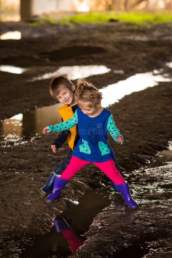 Ungar som spelar i gyttja fotografering för bildbyråer
