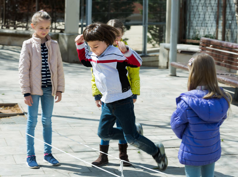 Ungar som spelar i lek för hopprep arkivbild