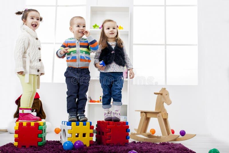 Ungar som spelar i rummet arkivbild