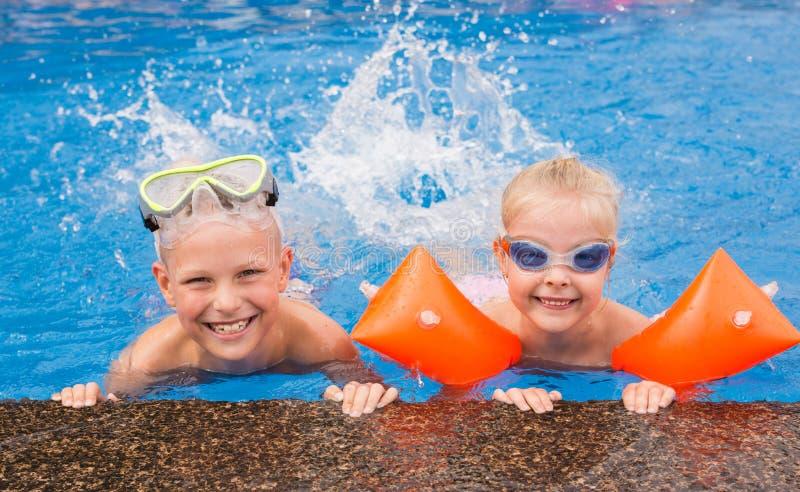 Ungar som spelar i simbassängen arkivbild