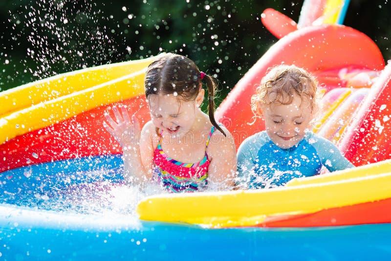 Ungar som spelar i uppblåsbar simbassäng royaltyfria foton