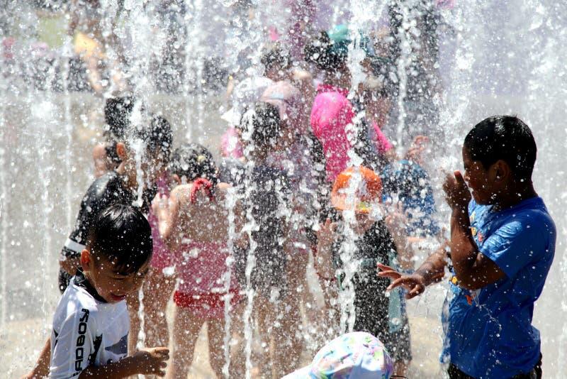 Ungar som spelar i vattenspringbrunnen i en varm dag royaltyfria bilder