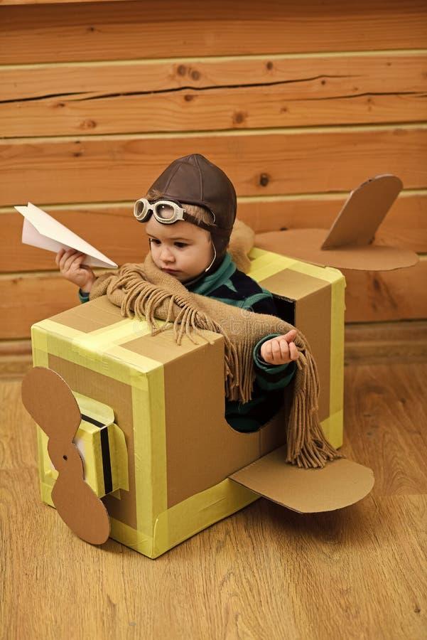 Ungar som spelar - lycklig lek Liten drömmarepojke som spelar med ett pappflygplan royaltyfri bild
