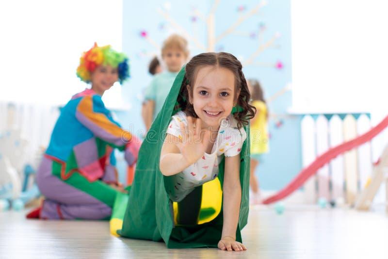 Ungar som spelar med clownen på födelsedagpartiet i underhållningmitt royaltyfri foto