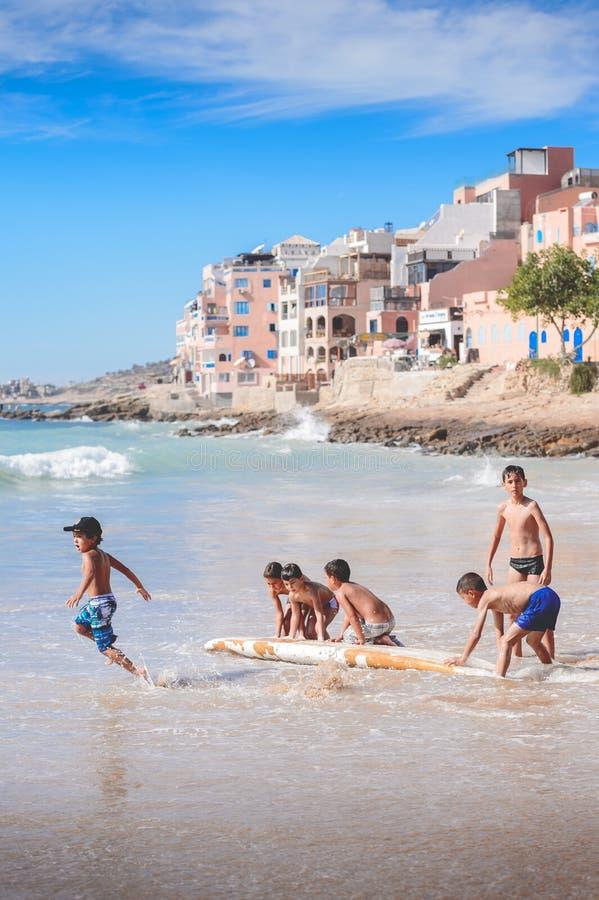 Ungar som spelar med den gamla surfingbrädan, Taghazout bränningby, agadir, Marocko 2 royaltyfri fotografi