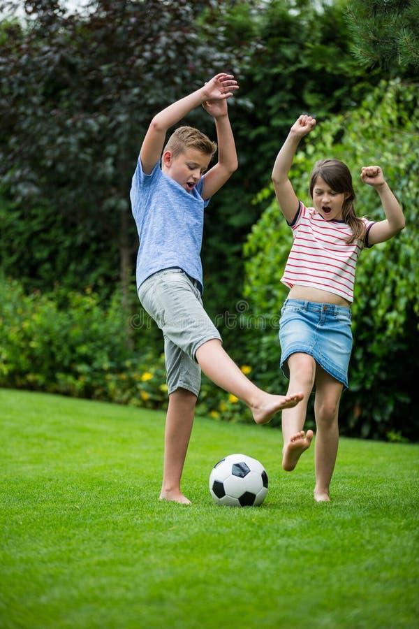 Ungar som spelar med fotboll parkerar in arkivfoton