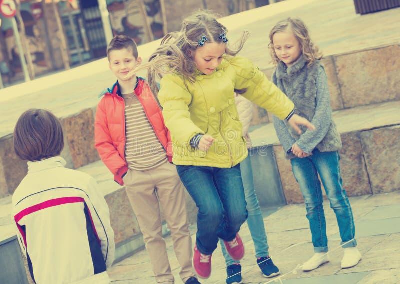 Ungar som spelar med hopprepet på gatan royaltyfria bilder