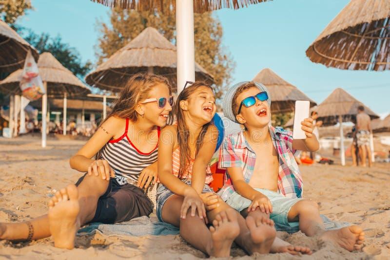 Ungar som spelar med mobiltelefoner på den sandiga stranden royaltyfri fotografi