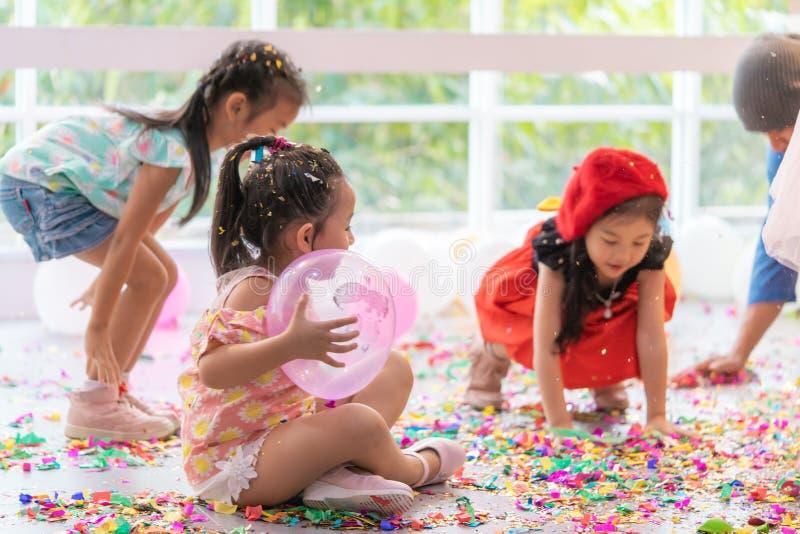 Ungar som spelar och kastar papper och ballongen i ungeparti royaltyfri foto